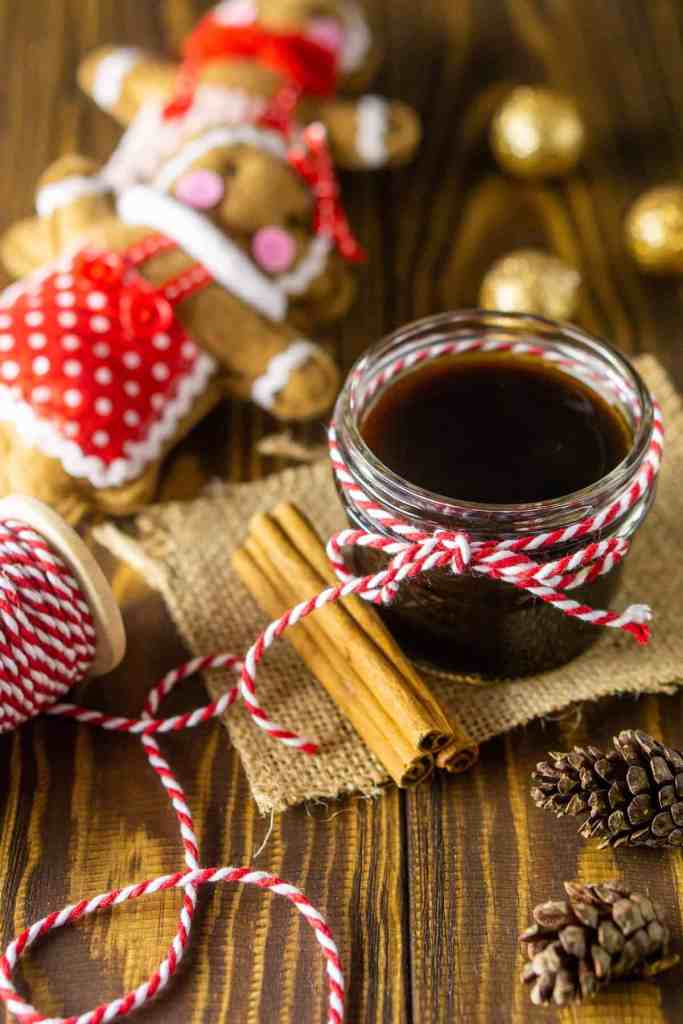 A small mason jar with a ribbon filled with homemade gingerbread simple syrup with cinnamon sticks and gingerbread people ornaments in the background.