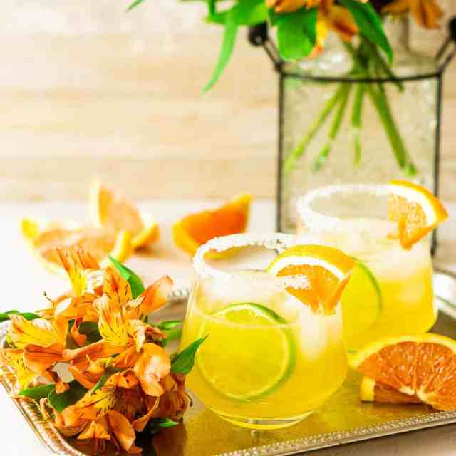 Two cara cara margaritas on a silver platter with orange flowers and Cara Cara slices to the side.