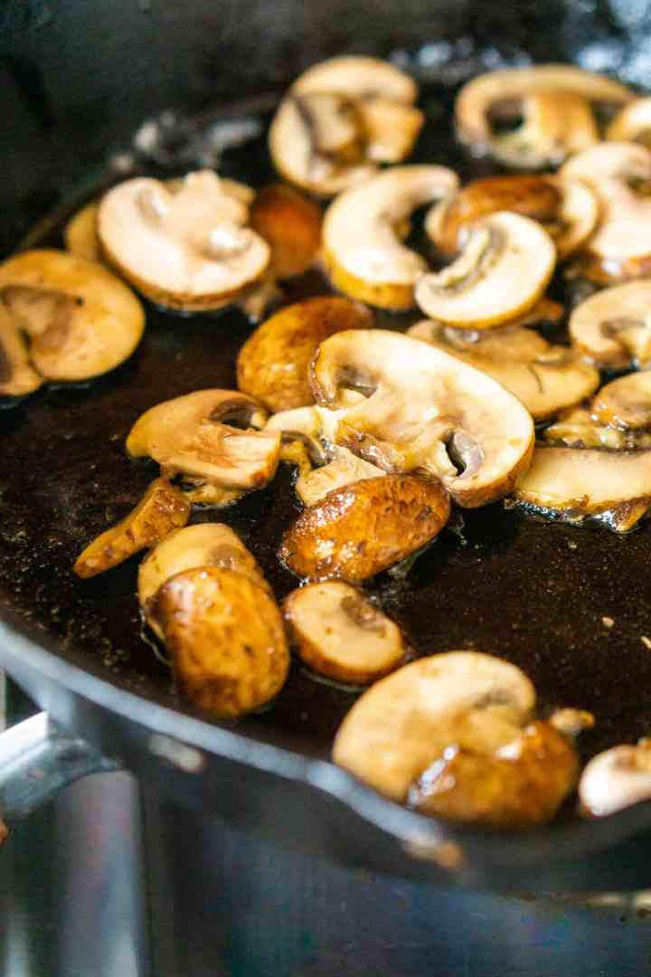 Browning the mushrooms in a cast-iron skillet with butter.