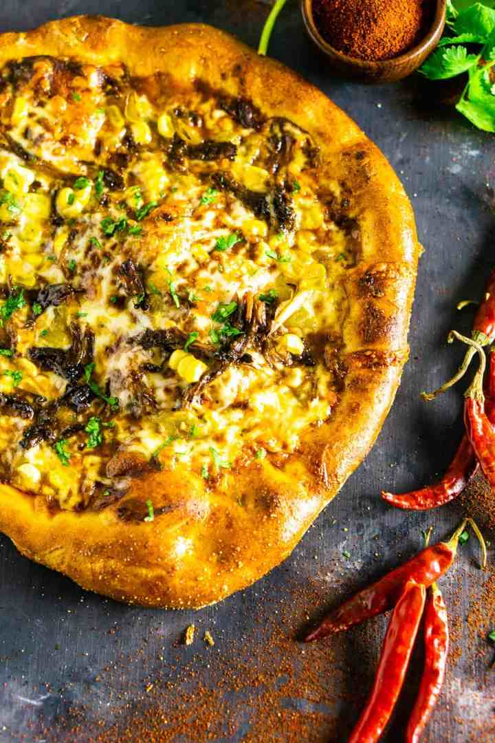 An aerial shot of the Mexican beef pizza on a slate board with dried chile peppers.