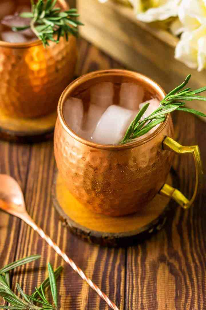Looking down into a mule with the copper bar spoon and a rosemary sprig to the side.