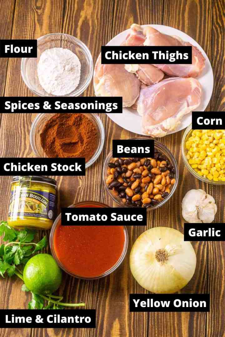 The ingredients for the Instant Pot chicken enchilada soup on a wooden board with black and white labels.