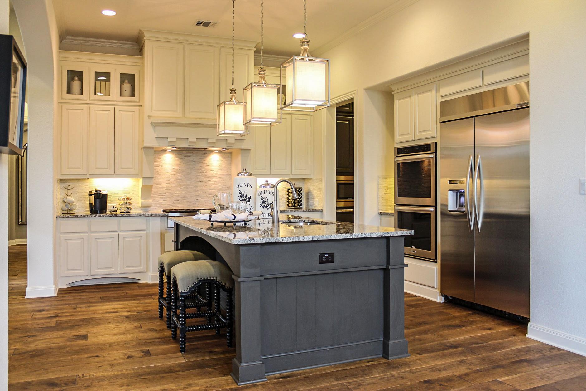 Kitchen cabinets in bone white with custom wood vent hood