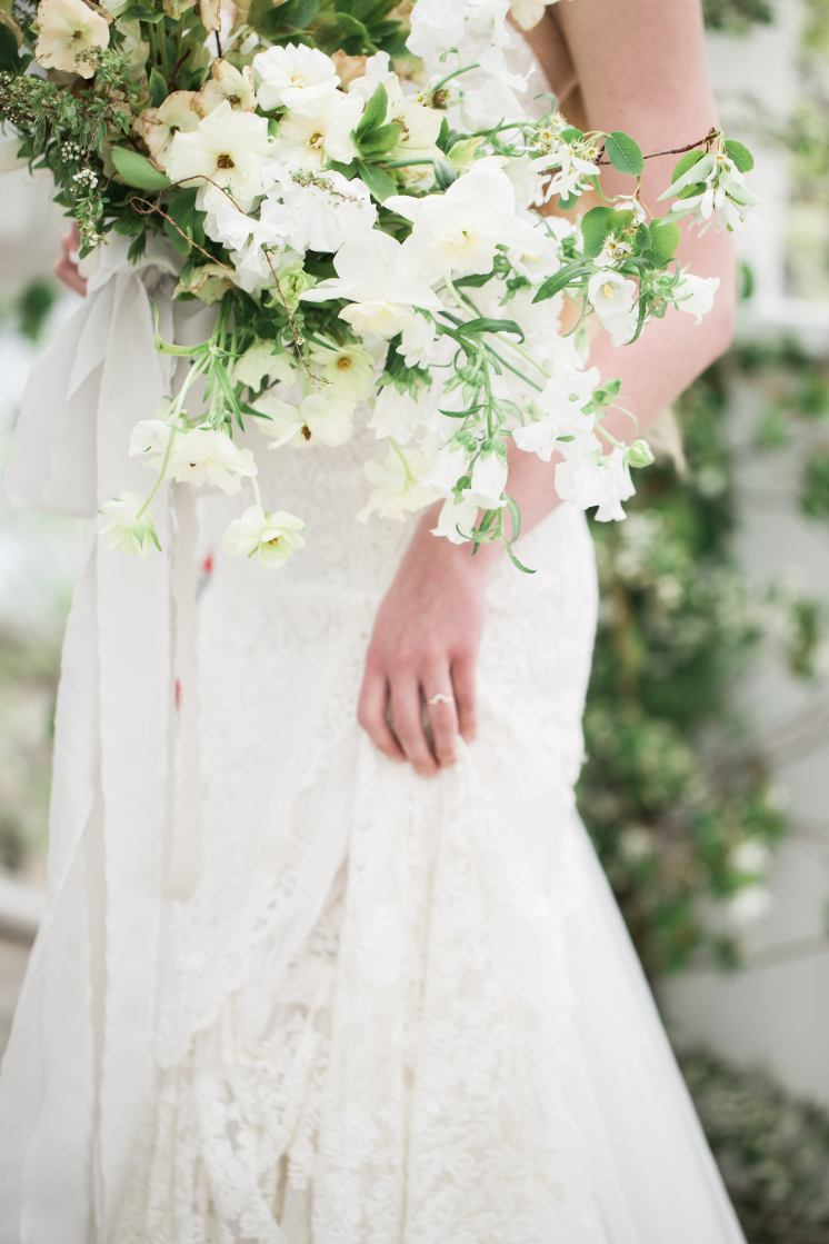 A Brides Dress And Bouquet Of Flowers