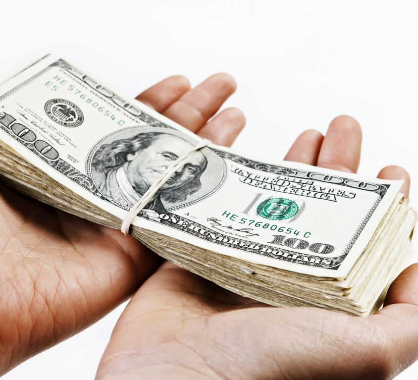 Hands hold out large bundle of US dollars