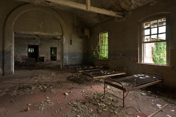 Algunas camas de los pacientes permanecen en el lado sur de algo más intacto del edificio.