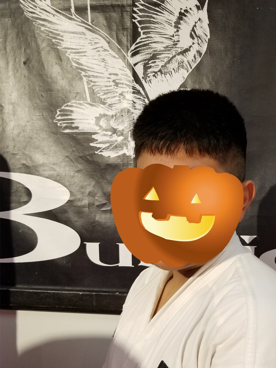 karate teen hidden by pumpkin