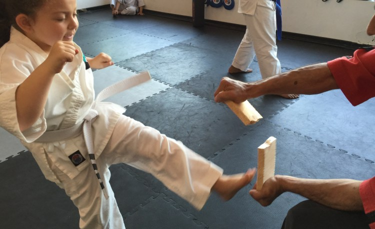 young karate girl breaks board