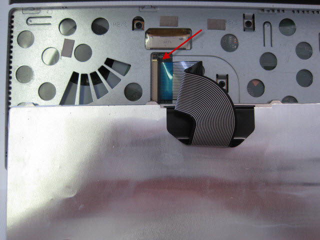 The keyboard is connected using a ribbon. To detach the ribbon from the laptop gently lift the brown retaining clip.