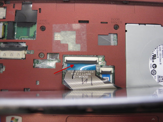 Arrow points to brown catch that needs gently lifting to release the keyboard ribbon cable.