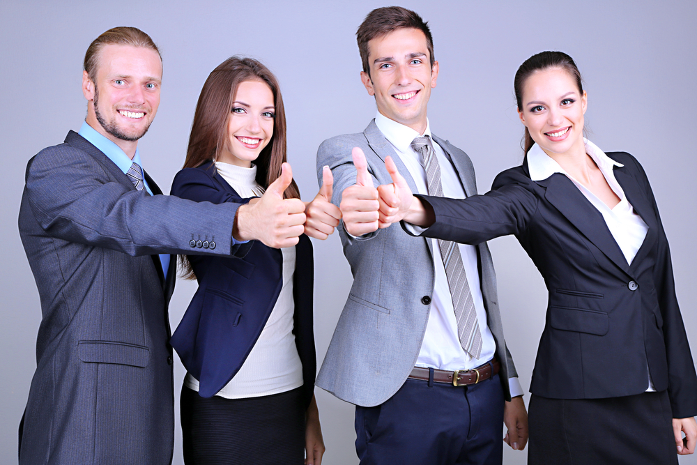 Business men and women giving thumbs up