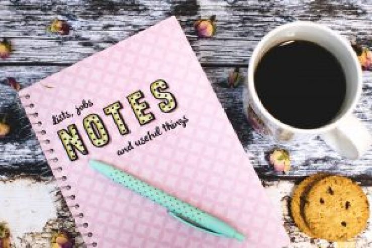 A pink notebook, green polka dot pen, cup of coffee and two cookies on a desk