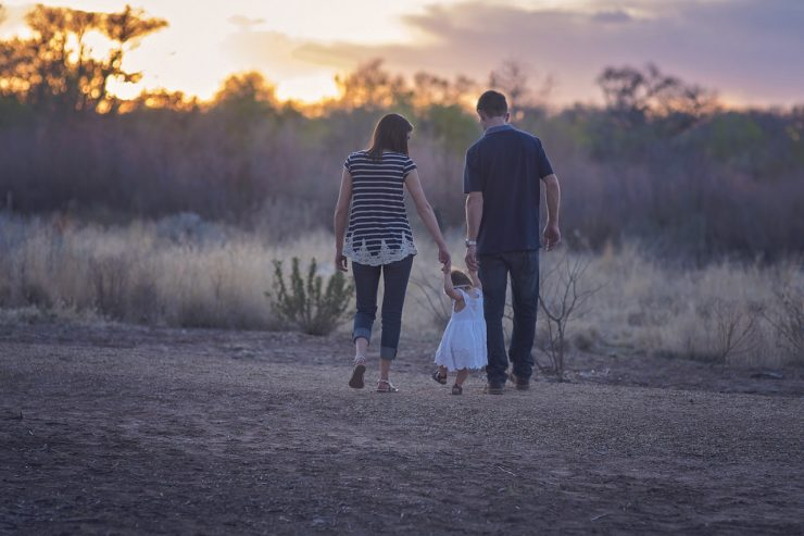 Young couple with toddler walking in the sunset