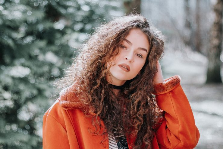 Woman with long curly hair wearing orange coat