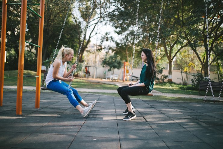 Two women in jeans and trainers sit opposite each other on swings