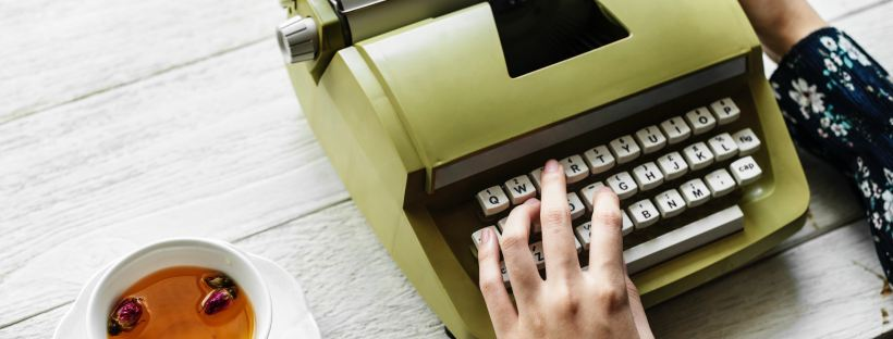 Green typewriter with a hand typing and a cup of tea - How do bloggers make money