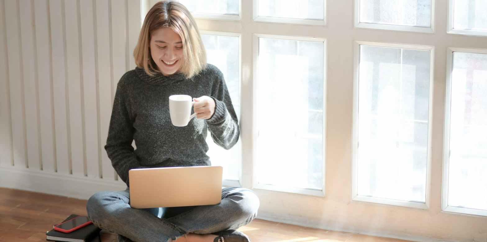 woman in gray sweater drinking coffee