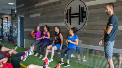 Core Progression. People leaning against a wall squatting and passing a ball while others sit on the floor exercising and a trainer watches.