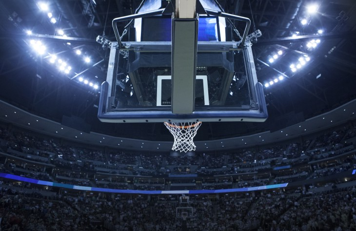 Brightly lit NCAA Basketball backboard in a large sports arena.