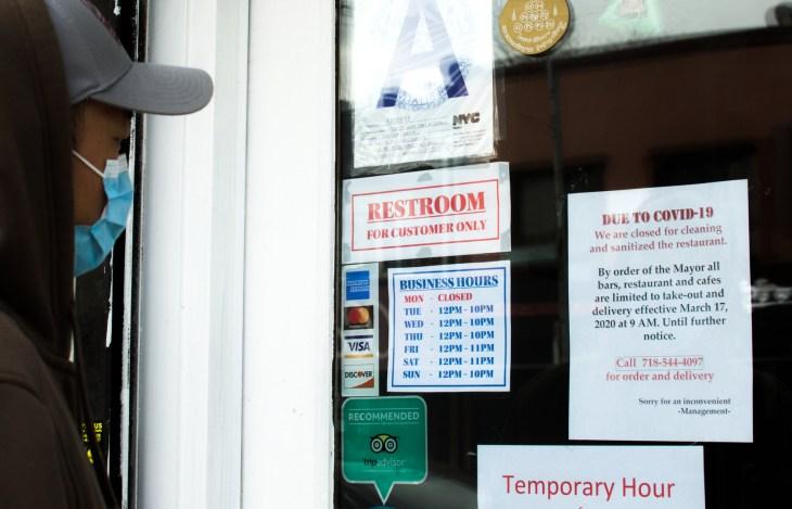 New York City, NY/ USA- 4-05-20: Person Looking at Closed Restaurant Sign Covid19 Coronavirus Pandemic Lockdown