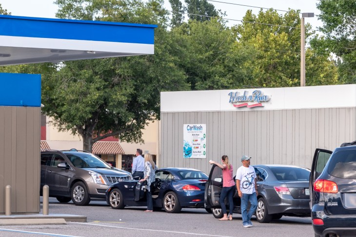 Oviedo, FL / USA - August 29, 2019: Residents of Oviedo, Florida get out of their cars while waiting in long lines for gas during Hurrican Dorian