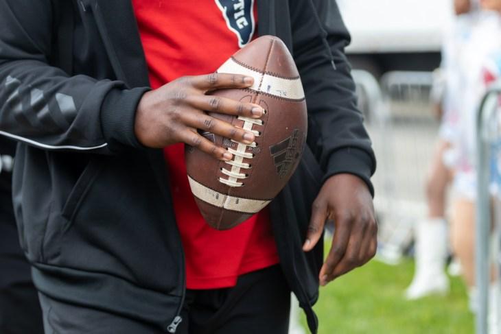 Boca Raton, Florida/USA - December 21, 2019: Florida Atlantic Owls vs SMU Mustangs. Cheribundi Boca Raton Bowl 2019. Afro-American man holding football ball in a hand