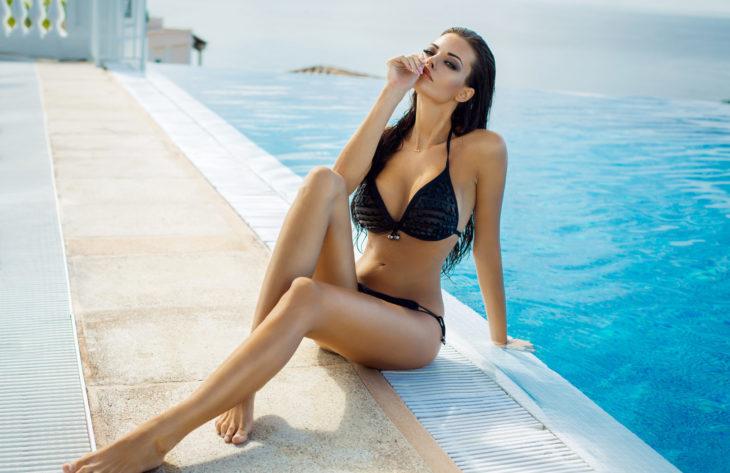 Beautiful woman wearing black bikini by the pool in summer scenery