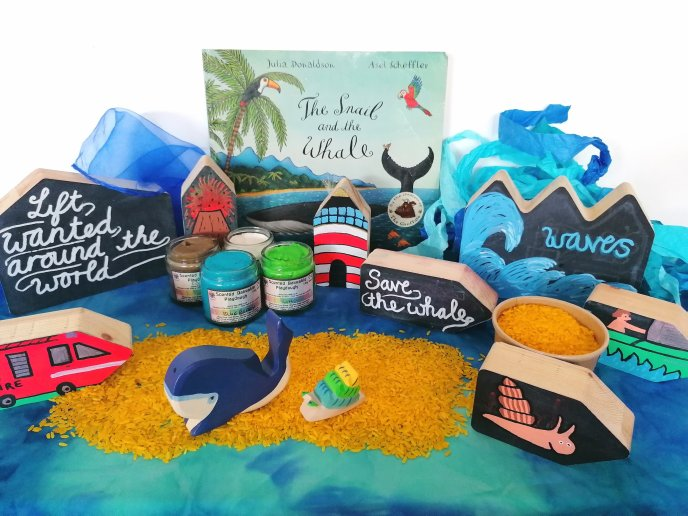 Story Sack for the Snail and The Whale with rice, playdough, decorated chalk houses, and whale and snail Holztoger figures