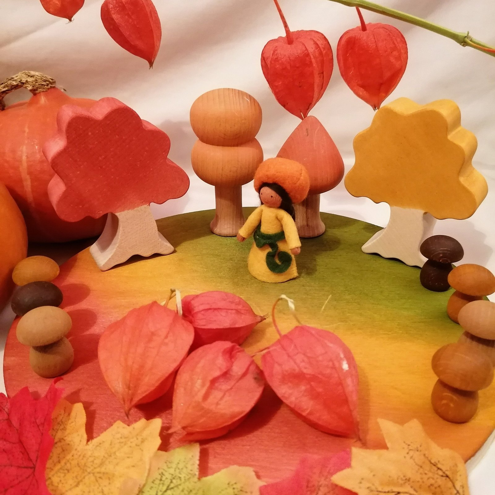 Small world homemade nature table display with woodstained board and trees with Ambrosious Pumkin fairy and natural loose parts