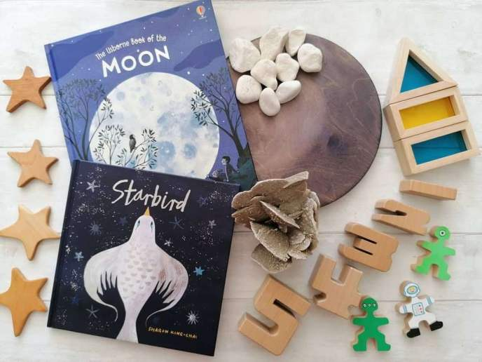 Starbird book flatlay with the Usborne Book of the Moon, four wooden stars to the left of the book. A hand stained moon wooden disc with white rocks and desert rose rock, to the right are the numbers 1 to 5 using SumBlox blocks. Flockmen (small wooden people) painted as two aliens and an astronaut with blue and yellow rainbow blocks to form a rocket.