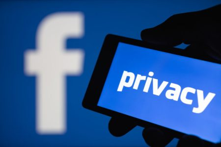 A smartphone in hand displaying the privacy text. Logo of the Facebook blurred on background. The concept of privacy on popular social network.