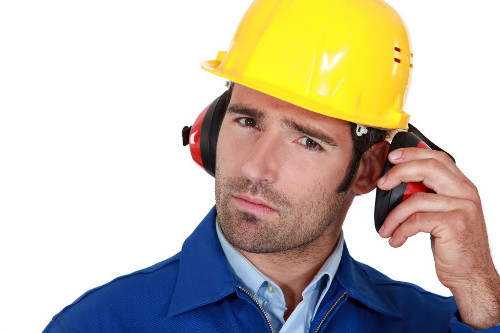 Man wearing safety PPE earmuffs and helmet.