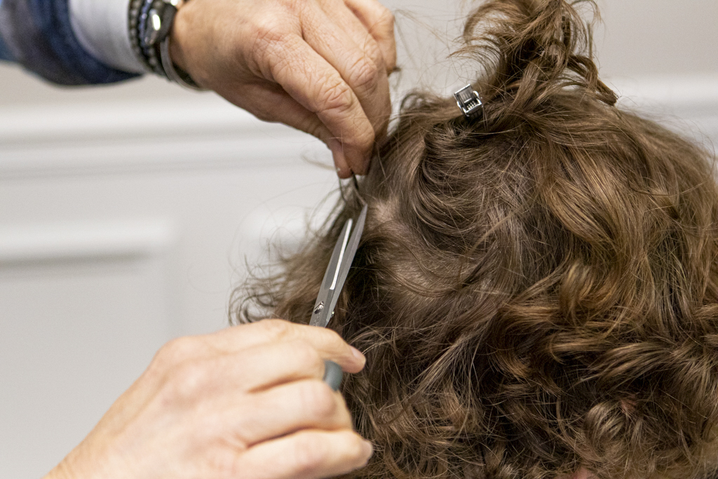 A collector from Butterfield Onsite Drug Testing is trimming a man's hair for a hair follicle drug test.