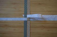 Schritt 7: Den rechten Streifen nach links unter der entstandenen Lasche durchziehen.