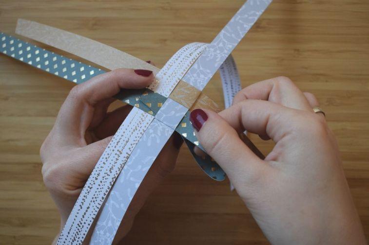 Schritt 12: Nun wird das Ende des Streifens durch die Lasche geführt. Wenn die kleine Zacke dabei nach hinten gedrückt wird, lässt sich der Streifen einfach durchziehen.