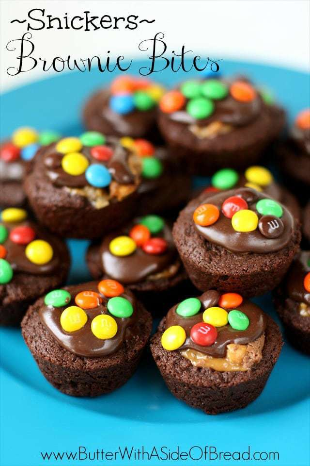 Snickers Brownie Bites made from homemade brownie recipe then stuffed with Snickers bites and topped with chocolate frosting and chocolate candies.