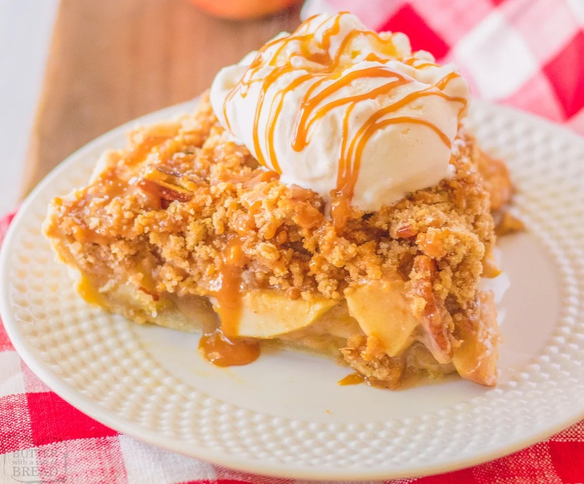 apple pie topped with vanilla ice cream and caramel on a white plate