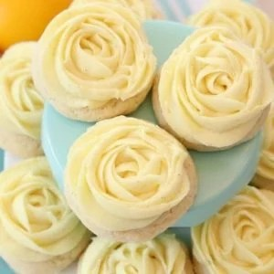 Lemon Sugar Cookies made with fresh lemon juice and zest in a soft sugar cookie dough and topped with a bright lemon buttercream frosting. Lemon Sugar Cookies are piped with a super simple rosette so they taste incredible and they're pretty too! No rolling and chilling necessary- just scoop, bake, cool and frost.