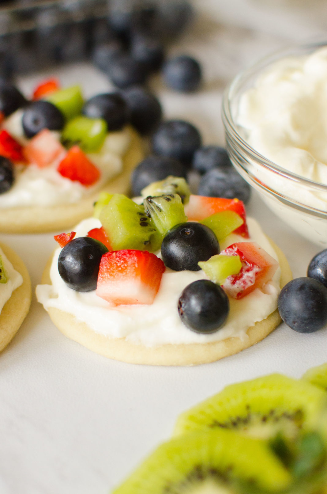 Fruit Pizza Cookies are all the goodness you get in a fruit pizza individualized! Soft crust, vanilla whipped cream frosting, topped with your favorite fruits; strawberries, raspberries, blueberries, kiwi, blackberries, mango.. the possibilities are endless!