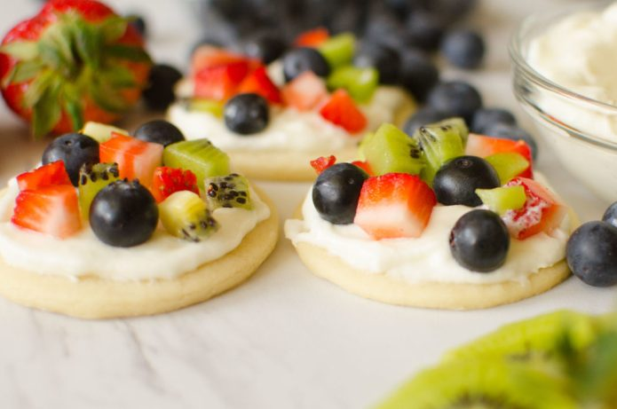 Fruit Pizza Cookies are all the goodness you get in a fruit pizza individualized! Soft crust, vanilla whipped cream frosting, topped with your favorite fruits; strawberries, raspberries, blueberries, kiwi, blackberries mango.. the possibilities are endless!