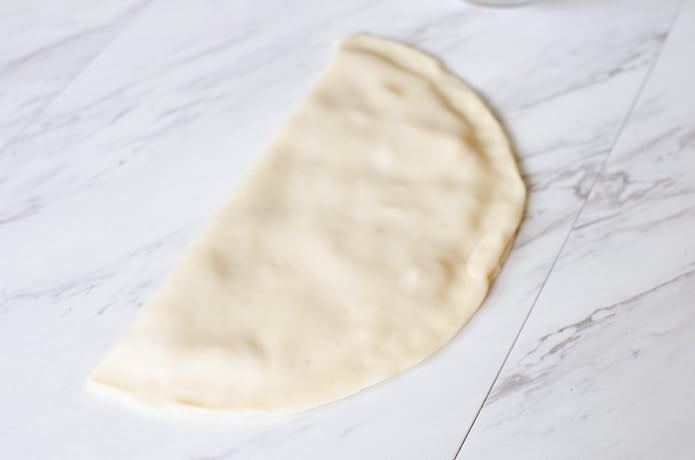 Pie crust with apple sauce inside.