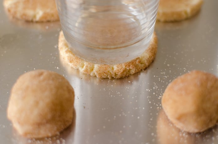 flattening the cookie dough balls with the bottom of a drinking glass