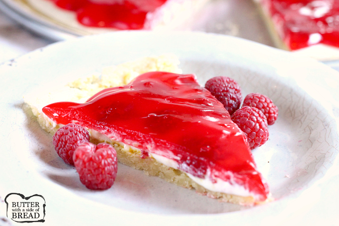 Lemon Raspberry Fruit Pizza is made with a lemon sugar cookie crust that is topped with a cream cheese layer, fresh raspberries and a delicious raspberry glaze! This fruit pizza recipe is so easy to make by using a lemon cookie mix and the glaze is made with raspberry jello!