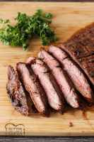 grilled flank steak on a wooden cutting board