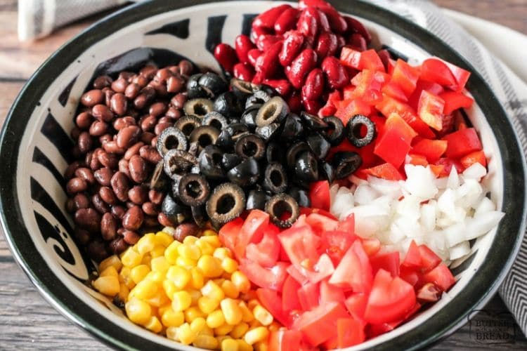 beans, tomatoes, onions, olives, corn and peppers in a bowl to make taco salad
