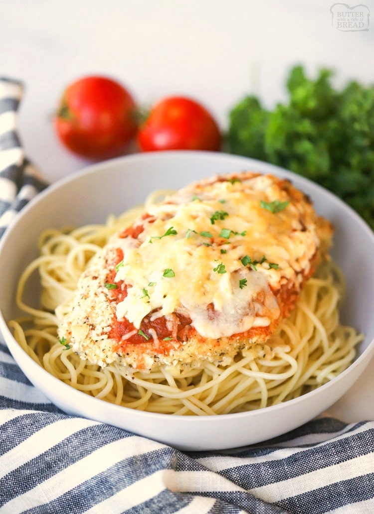 Baked parmesan chicken on top of spaghetti noodles
