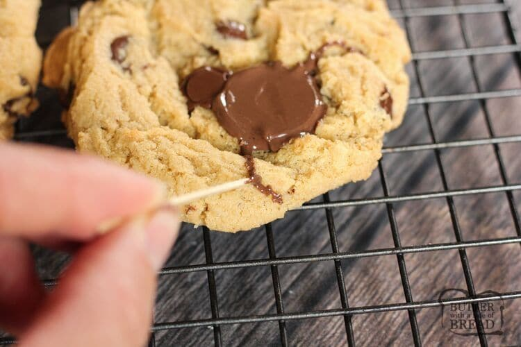 drawing a spider on a cookie with melted chocolate and a toothpick