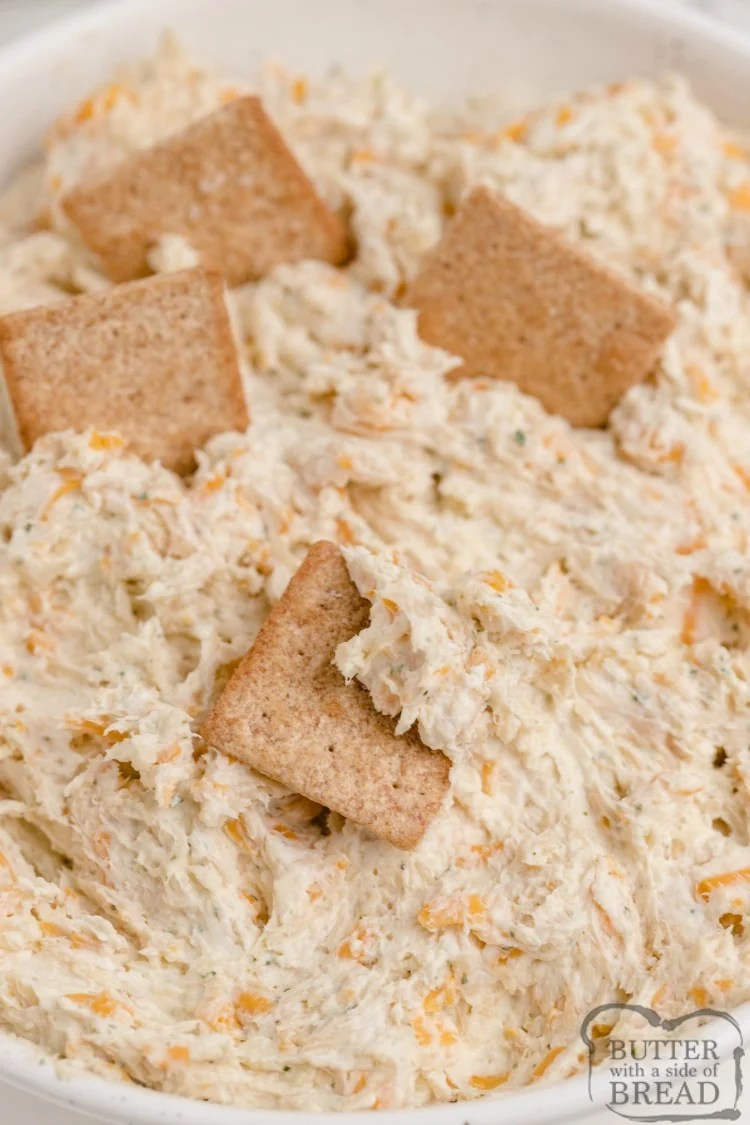 Dipping wheat thins in ranch dip with chicken and cheese