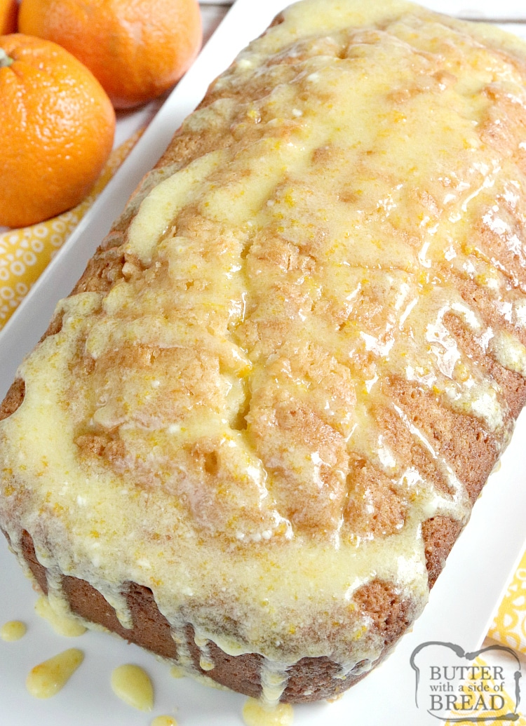 Loaf of orange quick bread with orange glaze on top.