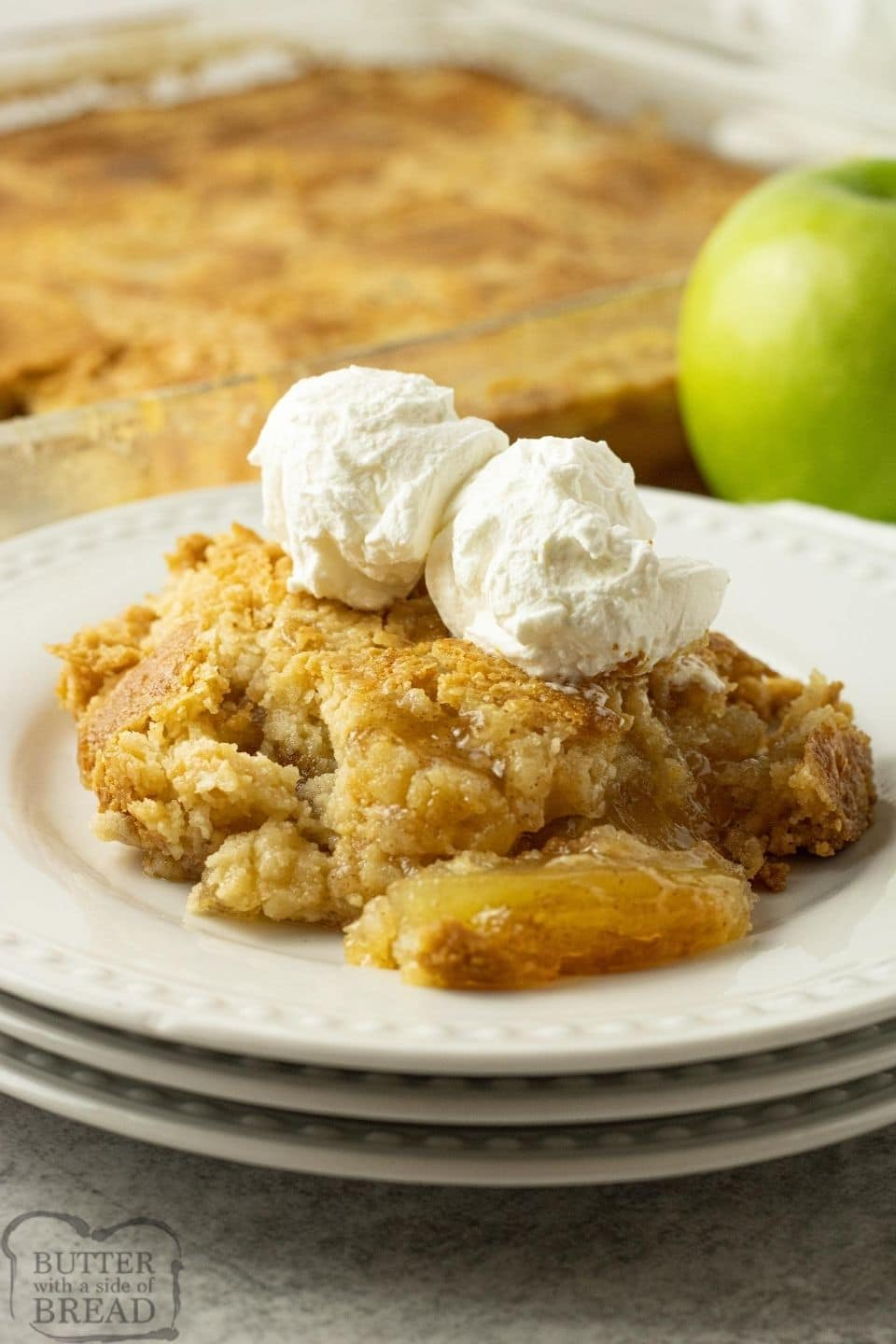apple dump cake on stacked white plates with whipped cream